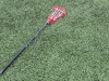 A player's lacrosse stick sits on the sidelines as the Stars take a warm up lap. by Maggie Allen