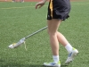 Sophomore Anne Nulton scoops up a ball during the STA vs. LSHS lacrosse game April 9. by Maggie Allen