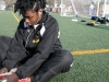 "Sophomore Kennedy Bright listens to music while stretching out before her event on the track invitational held at Bishop Miege High School April 5. ""€œI was getting ready for the 100 meter finals and I got first. It was my best time that I've ran this season."" by Viridiana Hernandez"