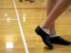 "Sophomore Claire Reboulet waits for instructions after putting on her dance shoes at STA's dance clinic April 17. ""I was kind of nervous so I kept moving around,"" Reboulet said. ""I had a lot of fun though."" by Viridiana Hernandez"
