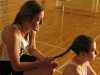 Senior Peyton Gajan, left, braids sophomore Anna Meagher'€™s hair in the gym in preparation for their game against Barat Academy Friday April 5. Many girls on the team wore braids for the anticipated intensity of the game. by Katie Hornbeck