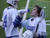 By: Claire Jefferson: Senior Mitch Holland grabs a drink while Senior John Quinly walks on the field before heading into the first half of the Rockhurst vs. Shawnee Mission East game, April 18th. The Rockhurst Hawklets defeated the Shawnee Mission East Lancers 7-6 in overtime. (Behind the Scenes)