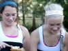 Sophomores Gabby Keller, left, and Meg Thompson grin while preparing their bagels before a tennis match against St. Joseph Central High School Sept. 25 at Homestead Country Club. Team parents provide snacks and drinks for the players to enjoy during their matches.
