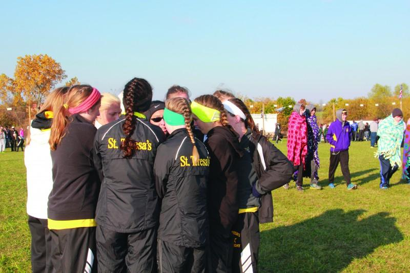 The+varsity+cross+country+team+huddles+together+with+head+coach+Karen+Moran+at+the+Class+4%2C+Sectional+4+meet+Nov.+9.+photo+by+Mary+Hilliard