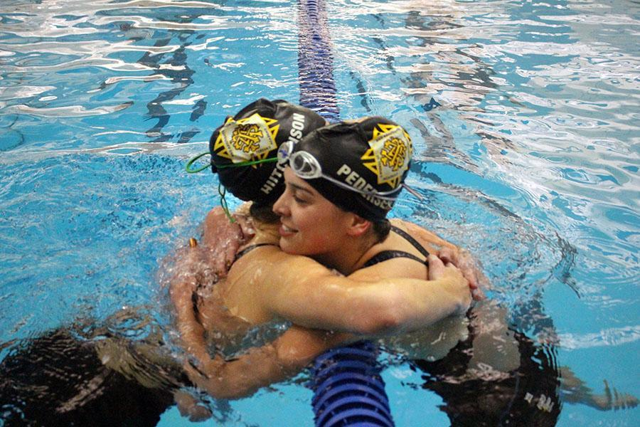 Junior Libby Hutchinson, left, hugs senior Darby Pedersen after getting her State cut in the 200 yard freestyle. Hutchinson won the event and Pedersen finished third.