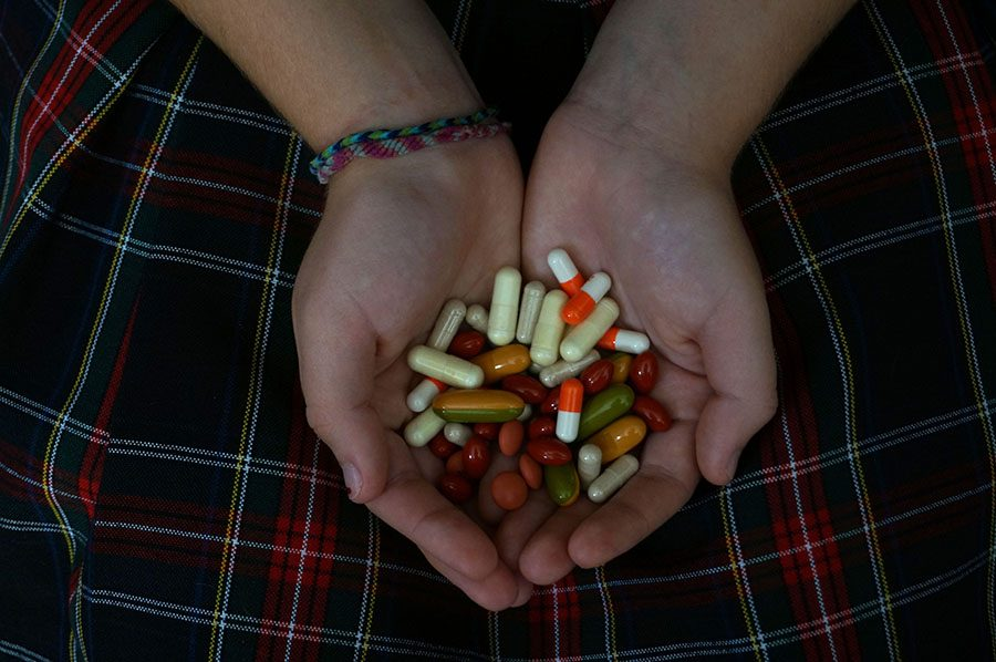 An+STA+student+holds+a+handful+of+pills.+photo+by+Gabby+Martinez
