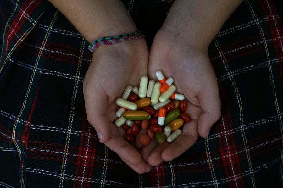 An STA student holds a handful of pills. photo by Gabby Martinez