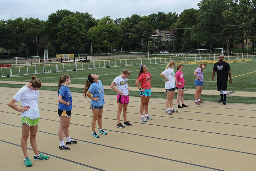 Coach Steve Redmond, far right, leads the girls in the 8-week conditioning program in stretches between each workout. photo by Anna Louise Sih
