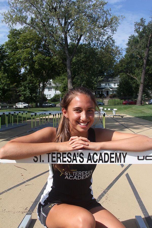 Junior+Mia+Schloegel+poses+for+a+photo+by+a+track+hurdle.+Schloegel+has+been+on+varsity+cross+country+since+she+was+a+freshman.+photo+by+Gabby+Ayala