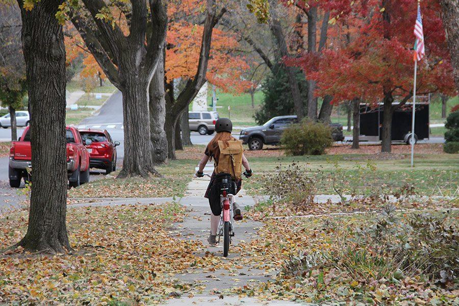 Junior+Isabella+Fitzpatrick+rides+her+bike+down+the+sidewalk+of+E+56th+Street+after+school+Nov.+22.+photo+by+Alex+Davis