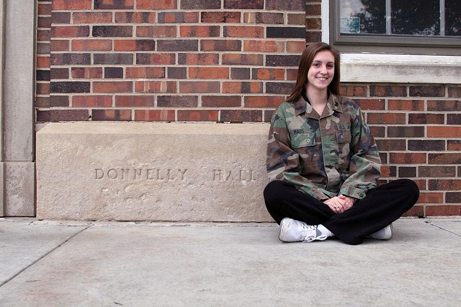 Senior Nicole Maus sits in front of the Donnelly building Nov. 21. Maus donned her mother's army jacket, used during her time in the service. photo by Cassie Hayes