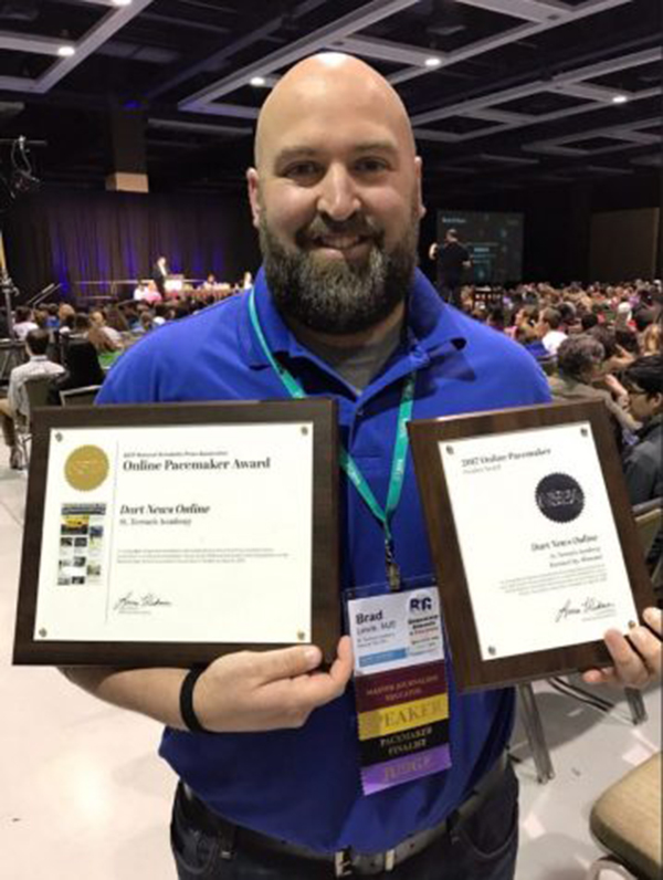 Dart and Teresian adviser Brad Lewis holds up the Dart's Pacemaker finalist award and award winner plaques. Lewis attended the NHSJC (National High School Journalism Convention) in Seattle, WA to receive the award winner plaque for STA. photo courtesy of Jim McCrossen, Blue Valley Northwest High School