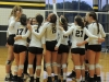 Students on the STA varsity volleyball team talk and celebrate in a huddle after defeating Sion in two of three sets at the game in Goppert Sept. 16. photo by Maddy Medina