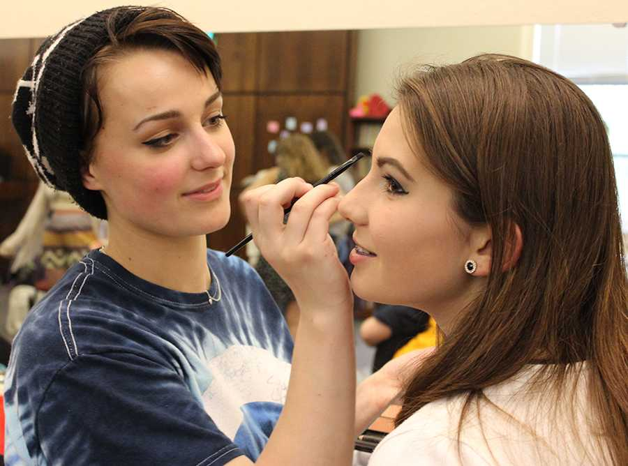 Sophomore Emma Gustavson, left, applies makeup to freshman Katelyne Kratofil for Student Productions April 24. photo by Bridget Jones