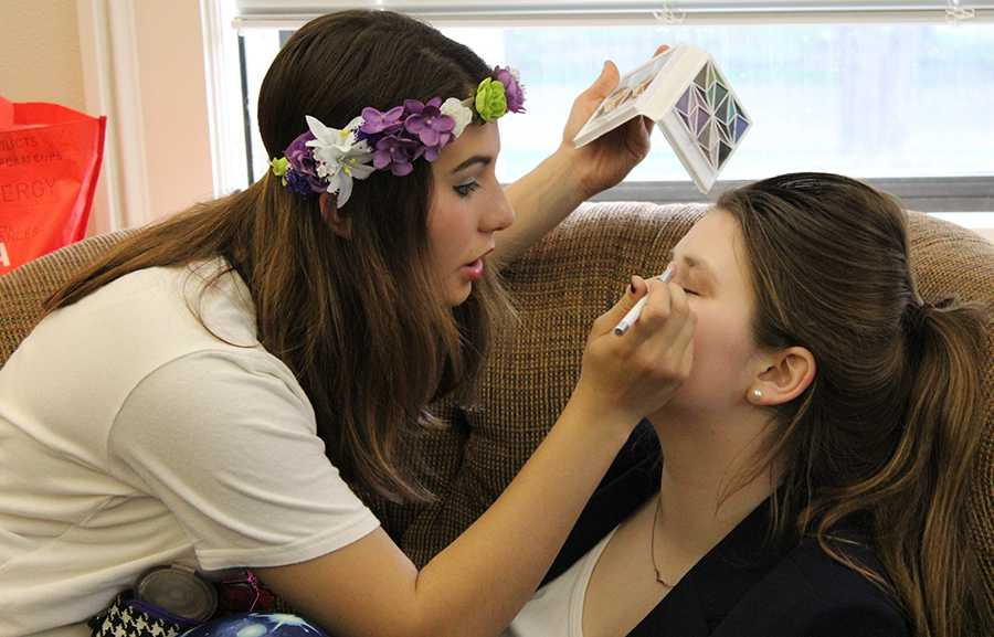 Freshman Katelyne Kratofil, left, helps freshman Claire Molloy with her makeup for Student Productions April 24. photo by Bridget Jones