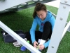 Sophomore Haley Baldwin finds shelter to lace up her spikes  for her last workout in preparation for the Kansas Relays at the Coppinger Track April 17. by Kennedy Bright