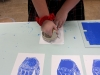 A hand stamp was placed on top of the sheet of glass with the royal blue paint previously. As shown in this picture, the stamp was pressed onto a small sheet of paper. photo by Sophie Sakoulas