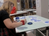 Senior Caterina DeRousse paints intricate detail to her hand designs using the Linoleum block printing technique in art teacher Theresa Wallerstedt's room. photo by Sophie Sakoulas