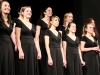 The STA Singers choir smiles for their applause during their performance Jan. 27. The girls were led by choir teachers Greg Monsma and Steven Karlin. photo by Maggie Knox