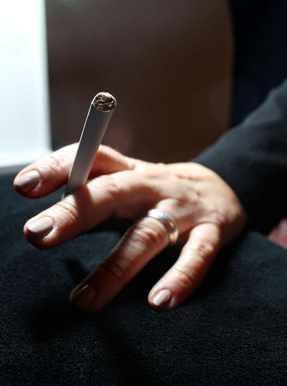 A tobacco cigarette rests between two fingers waiting to be lit. In mid-November, the Kansas City, Mo. City Council and Kansas City, Kan.  Unified Government Board of Commission passed an ordinance raising the legal age to buy nicotine and vapor products from 18 years old to 21 years old. photo illustration by Kat Mediavilla