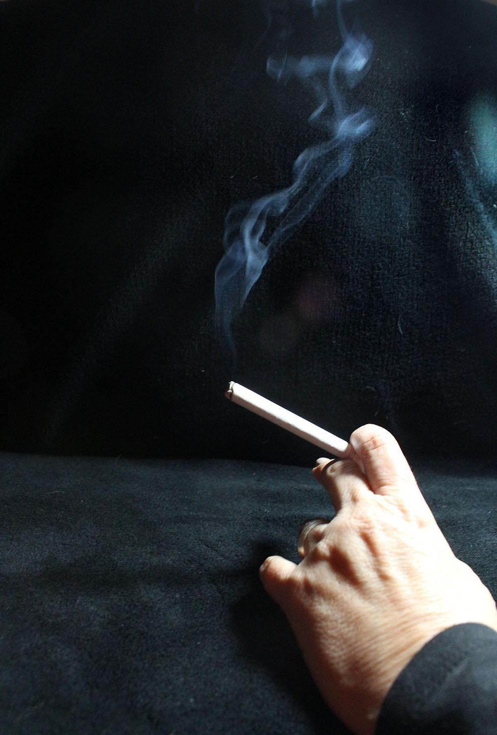 A hand holding a lit cigarette rests on a table. In mid-November, the Kansas City, Mo. City Council and Kansas City, Kan.  Unified Government Board of Commission passed an ordinance raising the legal age to buy nicotine and vapor products from 18 years old to 21 years old. photo illustration by Kat Mediavilla