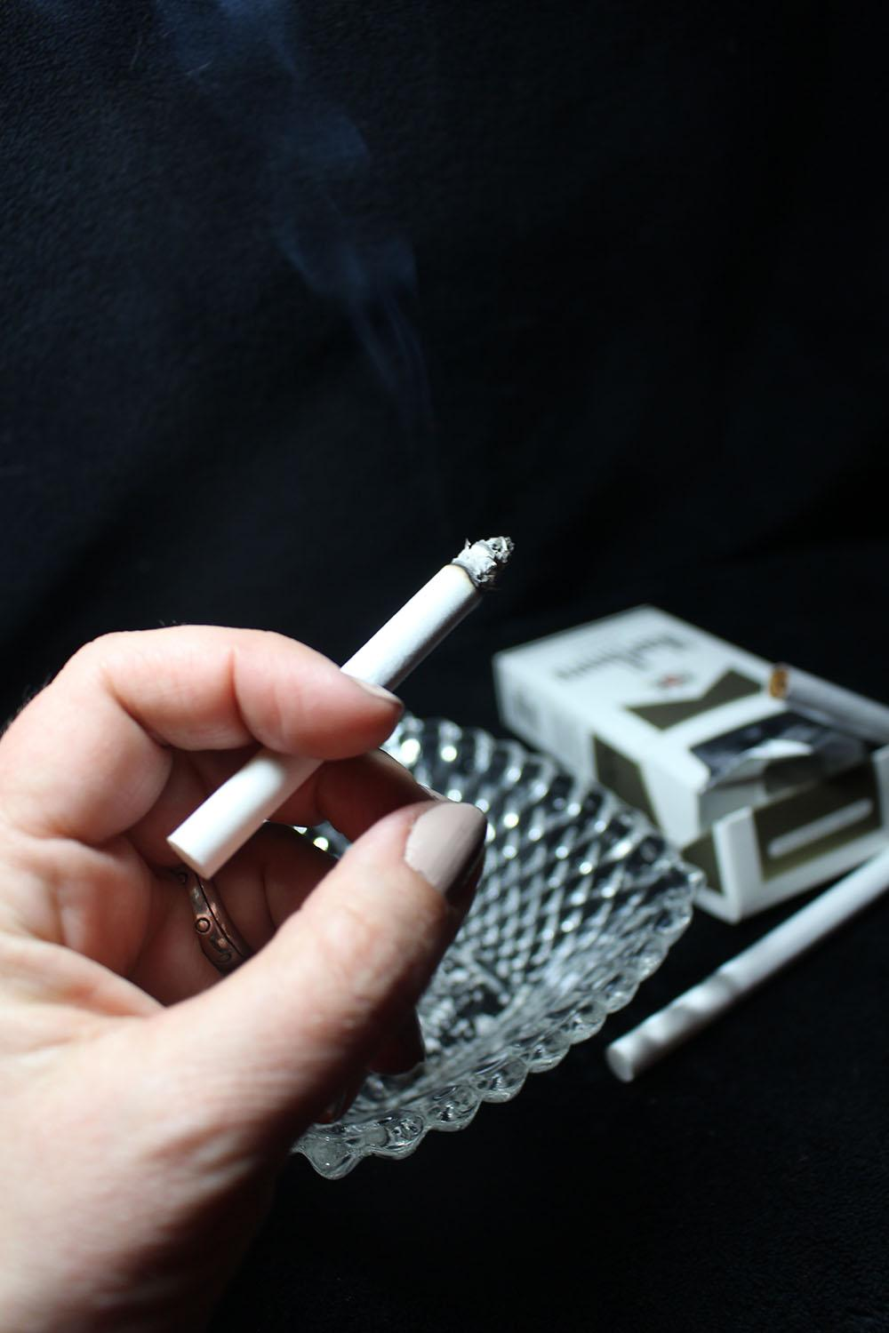 A hand holding a lit cigarette rests over an ash tray. In mid-November, the Kansas City, Mo. City Council and Kansas City, Kan.  Unified Government Board of Commission passed an ordinance raising the legal age to buy nicotine and vapor products from 18 years old to 21 years old. photo illustration by Kat Mediavilla