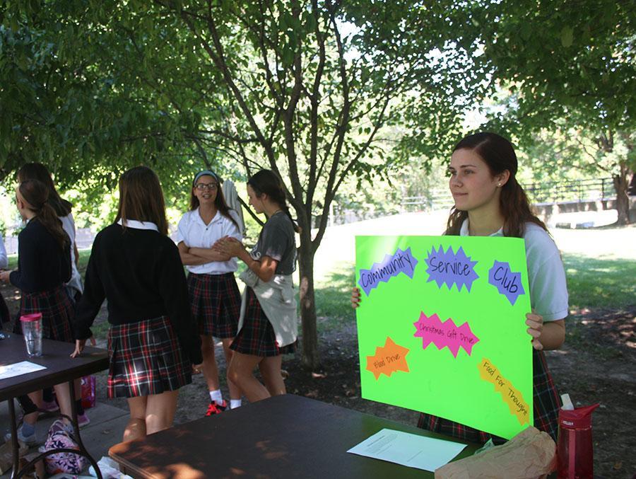 Senior Caitlin O\'Toole holds a sign at the Community Service Club\'s table at the club fair Aug. 24. photo by Bridget Jones