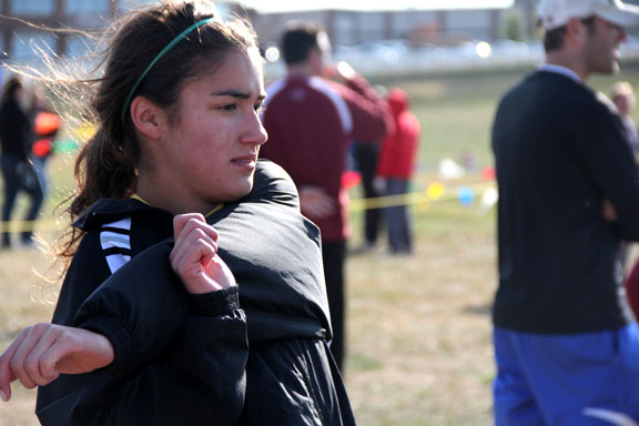 Senior Kelly O\'Byrne stretches before the varsity Sectionals cross country meet Saturday, Oct. 29.  O\'Byrne placed 35th at the meet and will advance to State with the rest of her team. Photo by Celia O\'Flaherty