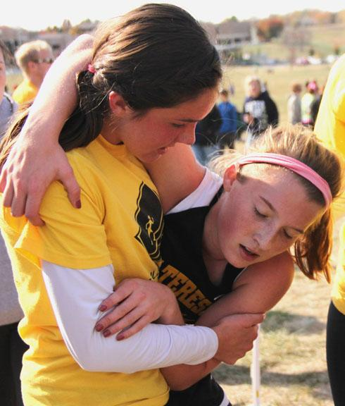 Junior Sarah Vickory, left, holds senior Lane Schulte as she crosses the finish line at the varsity alternate cross country Sectionals race. Schulte placed 64th in the race. Photo by Celia O'Flaherty