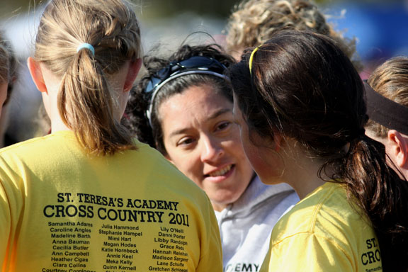 Head cross country coach Karen Moran talks in the huddle before the sectional meet. The team always talks and prays as a group before racing. Photo by Allison Fitts