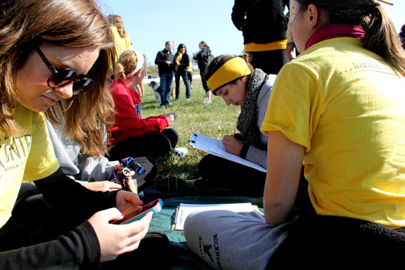 Junior Regan Stiles, left, and seniors Erin Sellers and Kate Rohr help compile race results at the sectional meet last Saturday. Photo by Allison Fitts