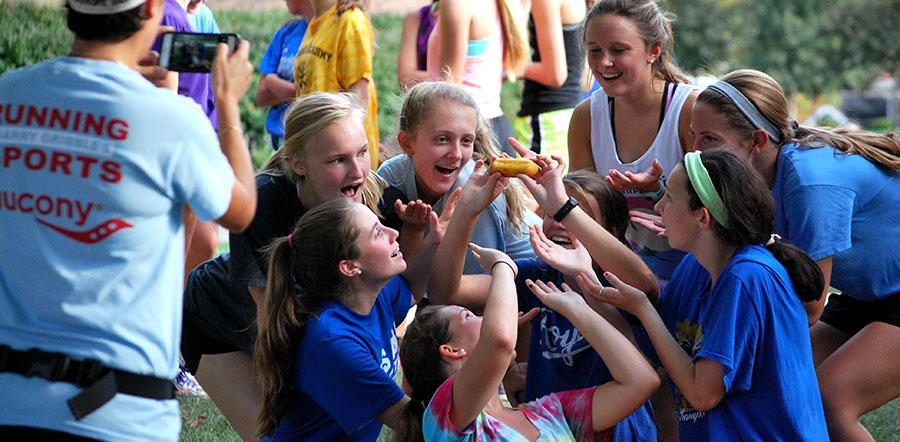 """Members of the cross country team pose for a picture with their """"baton"""" at the annual twinkie relay on October 8. photo by Libby Hutchison"""