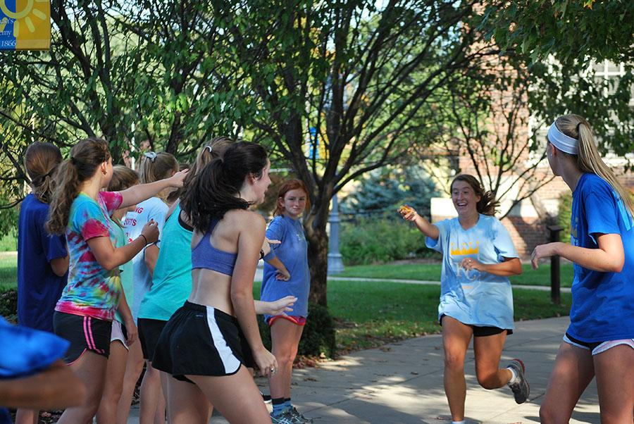 Senior Emily Laird hands off the Twinkie during the annual cross country Twinkie relay held at STA on October 8. photo by Libby Hutchison.