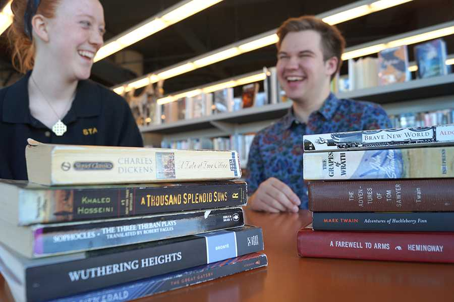 St. Teresa\'s senior, Grace Girardeau, and Rockhurst senior, Trey Hunt, laugh and chat at the Plaza Library. Some of their shared required reading includes, The Great Gatsby, Brave New World, and The Adventures of Huckleberry Finn. photo by Violet Cowdin