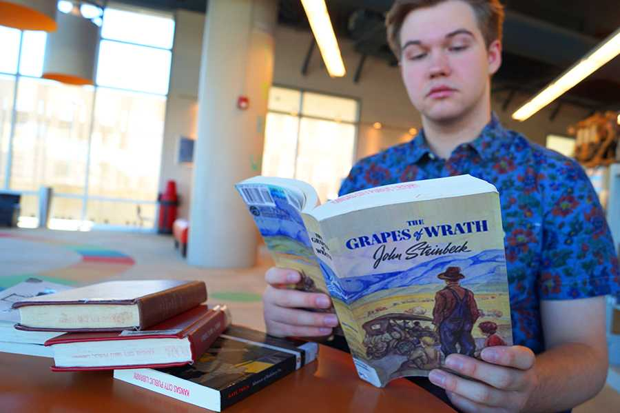 Rockhurst Senior, Trey Hunt, reads The Grapes of Wrath by John Steinback at the Plaza Library. The Grapes of Wrath is one of Hunt\'s required readings at Rockhurst. photo by Violet Cowdin