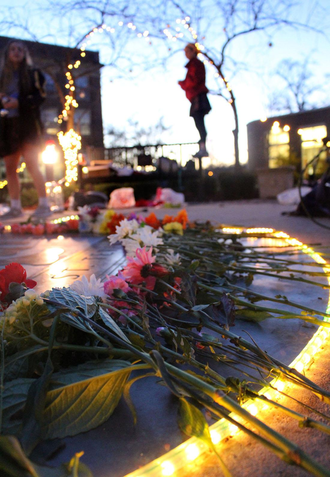 STA students gathered before school Wednesday Dec. 9 in honor of the two year anniversary of the death of STA alumna Becca Lueke. Flowers and pictures were placed on the seal in remembrance. photo by Kat Mediavilla