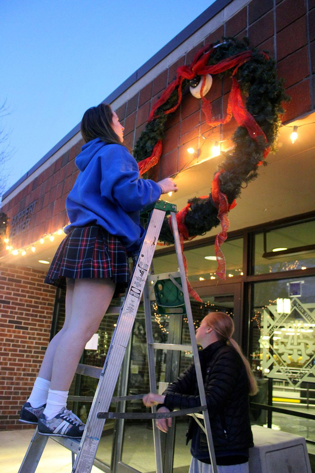 Senior Maddie Summers hangs a large wreath in front of the Goppert Center while classmate MaryMichael Hough assists. Students from the senior class gathered to decorate the quad for Christmas the morning of Dec. 9. photo by Kat Mediavilla