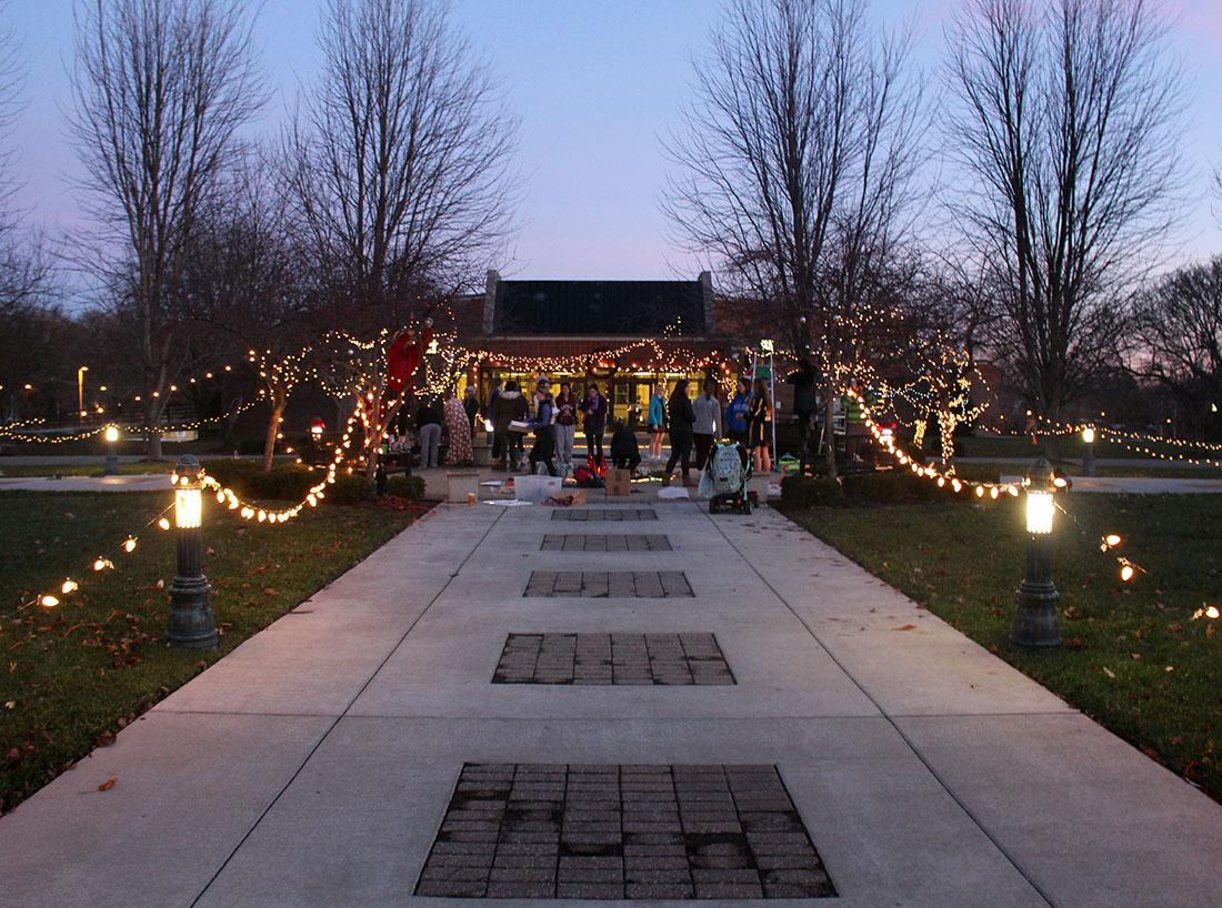 Senior students gathered before school Wednesday Dec. 9 to decorate the quad in remembrance of STA alumna Becca Lueke who passed away two years ago. Students decorated the quad with Christmas lights and left flowers on the seal. photo by Kat Mediavilla