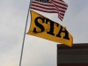 An STA flag is cast just below the American flag at Raymore-Peculiar High School. The flags were flown by the STA tailgate held before the District final basketball game. photo by Kat Mediavilla