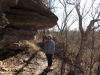 Senior Amber Brownlee poses and observes rock formations while on a hike in a wooded part of Kansas City Dec. 18. photo by Maddy Medina
