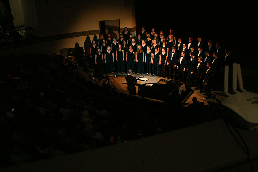 STA music teacher Steve Perry conducts the STA-Rockhurst choir as they perform in the M&A auditorium at the Fine Arts Showcase April 27. photo by Cassie Hayes