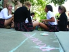 A group of students eat and converse during Frosh Fest activities Aug. 26. During the annual Frosh Fest chalk contest, many advisories focused on themes of sisterhood for their artistic inspiration. photo by Kat Mediavilla