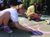 Senior Maggie Knox works alongside the Papinaeu advisory to complete a chalk design for STA's annual Frosh Fest. The Papinaeu advisory commemorated STA's 150th anniversary with their chalk art. photo by Kat Mediavilla