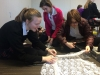 From left, junior Linden O'Brien-Williams, freshman Sophia Shugart and junior Reilly Johnson cut out sheets of lace for the lace-making project Feb. 3. photo by Paige Powell