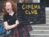 Senior Lilly McGonigle holds up a Cinema Club poster at the club fair Aug. 23.