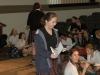 Senior, Rose Genaris, smiles as she passes out papers to Drama Club members. photo by Riley McNett