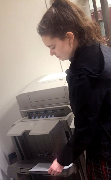 Junior Mary Keller picks up her paper from the printer before the bell rings. photo by Paige Powell