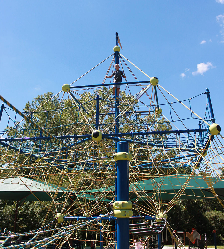Max Baker, a first grader from St. Elizabeth Catholic School,  reaches the top of a rope structure at Valley Park in Grandview, Missouri Aug. 21. photo by Meghan Baker