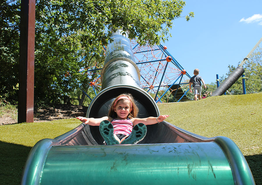 Molly Roudebush, a first grader at St. Thomas More Catholic School, goes down a slide at Valley Park in Grandview, Missouri Aug. 21. photo by Meghan Baker