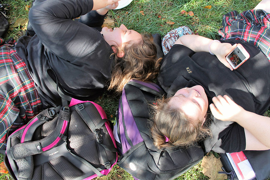 Sophomores Lauren Ennis and Maggie Hart lay in the quad at St. Teresa's Academy on Oct. 17. Photo by Meghan Baker.